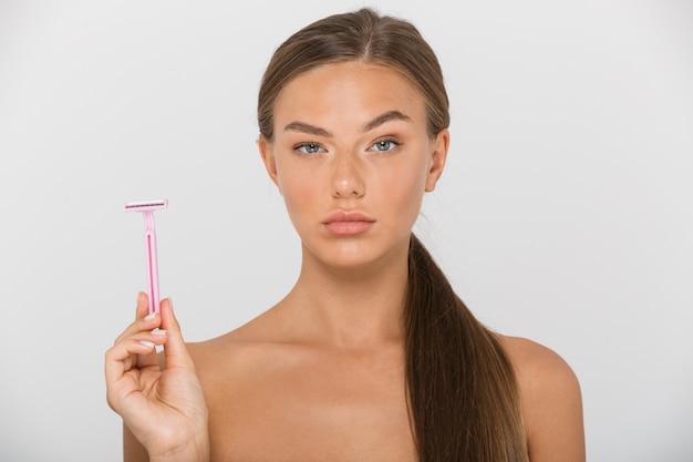 Schönheitsporträt der schönen hemdlosen frau mit dem langen braunen haar, das schreit und rasiermesser hält, lokalisiert