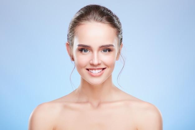 Schönheitsporträt der schönen lächelnden frau, graue augen. kopf und schultern der frau mit nacktem make-up, schönheitskonzept.