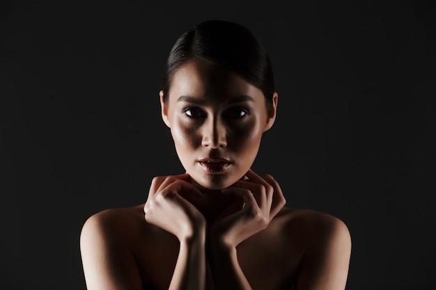 Schönheitsporträt der sexuellen kaukasischen frau mit dem braunen haar im brötchen mit dem schönen blick, lokalisiert über schwarzem