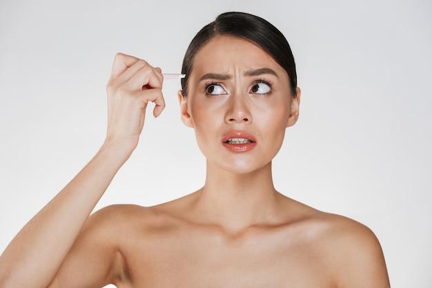 Schönheitsporträt der sinnlichen brunettefrau mit dem haar in den brötchengefühlsschmerz beim zupfen von augenbrauen mit der pinzette, lokalisiert über weiß