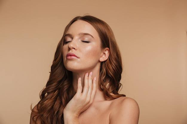 Schönheitsporträt der sinnlichen ingwerfrau mit dem langen haar, das mit geschlossenen augen aufwirft