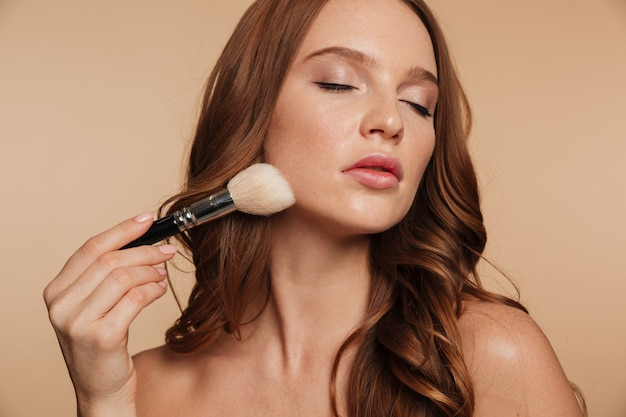 Schönheitsporträt der sinnlichen ingwerfrau mit dem langen haar und den geschlossenen augen, die kosmetik mit bürste auftragen