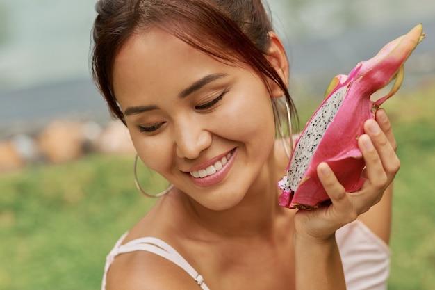 Schönheitsporträt des anmutigen asiatischen modells mit perfekter haut, die drachenfrüchte nahe gesicht hält.