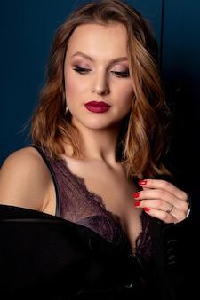 Schönheitsporträt des blonden luxusmodells mit perfektem make-up, das spitzen-bh und -jacke trägt