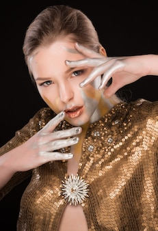 Schönheitsporträt des erstaunlichen blonden modells mit gold- und silberfarbe auf ihren schultern und im gesicht