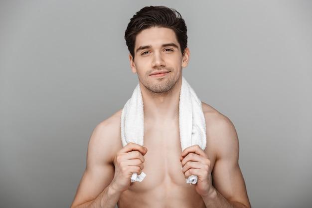 Schönheitsporträt des halbnackten lächelnden jungen mannes