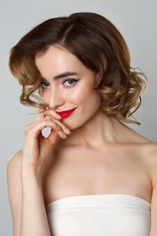 Schönheitsporträt des hübschen mädchens mit dem gelockten haar, katzenaugenmake-up, rote lippen