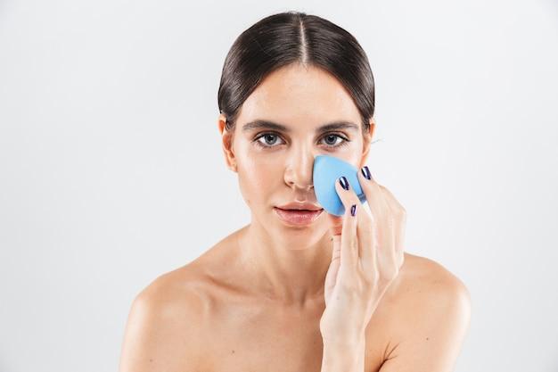 Schönheitsporträt einer attraktiven gesunden frau, die lokal über weißer wand steht und make-up-schwamm zeigt