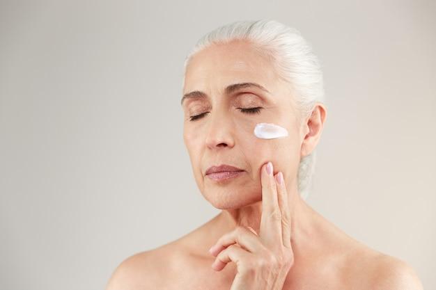 Schönheitsporträt einer attraktiven halbnackten älteren frau, die lippenstift hält und aufwirft