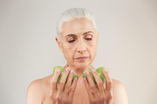 Schönheitsporträt einer attraktiven halbnackten älteren frau, die zwei scheiben des grünen apfels betrachtet
