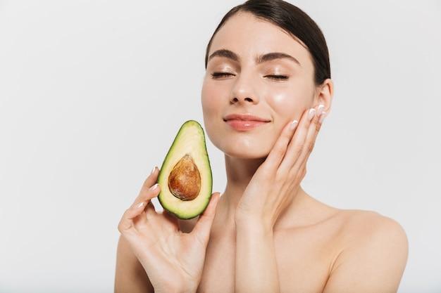 Schönheitsporträt einer attraktiven jungen brünetten frau, die isoliert über weißer wand steht und geschnittene avocado zeigt