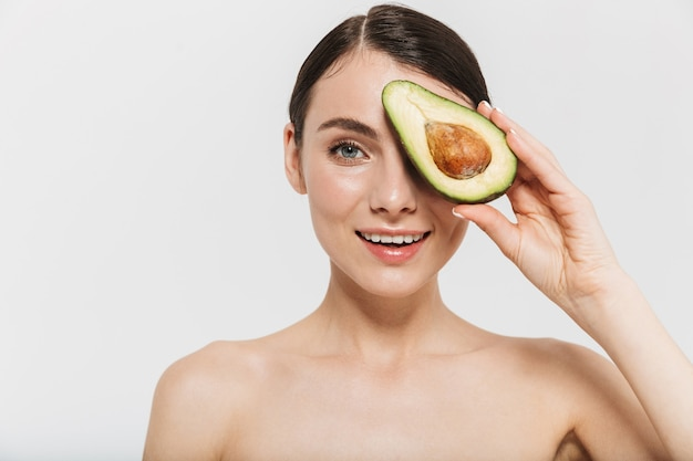 Schönheitsporträt einer attraktiven jungen oben ohne frau lokalisiert über weißer wand, die geschnittene avocado zeigt