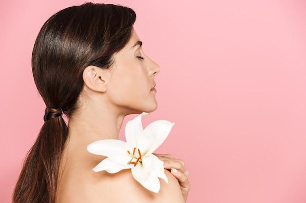 Schönheitsporträt einer attraktiven jungen topless-frau, die isoliert steht und mit lilienblume posiert
