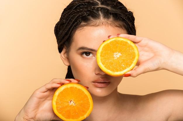 Schönheitsporträt einer attraktiven jungen topless-frau, die isoliert über beige wand steht und mit geschnittenen orangefarbenen früchten posiert
