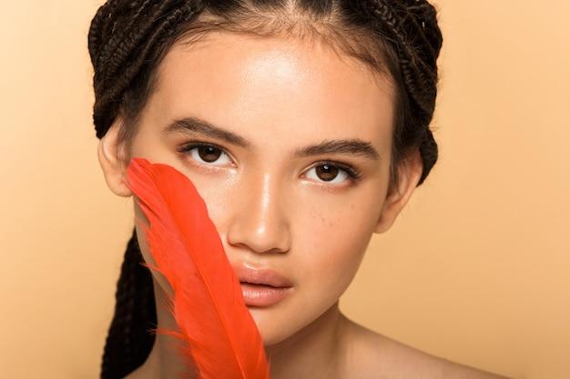 Schönheitsporträt einer attraktiven jungen topless-frau, die isoliert über beige wand steht und rote feder im gesicht hält