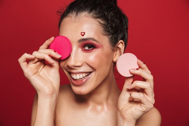 Schönheitsporträt einer attraktiven jungen toplessen frau, die make-up steht, isoliert