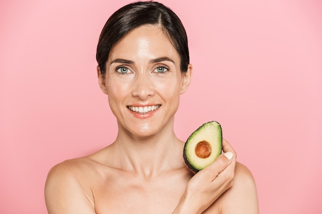 Schönheitsporträt einer attraktiven lächelnden gesunden topless brunettefrau lokalisiert, die geschnittene avocado zeigt
