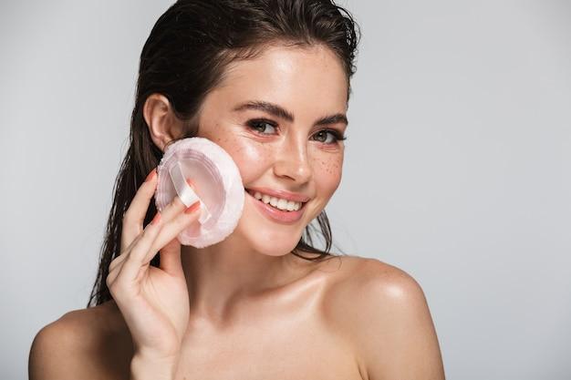 Schönheitsporträt einer attraktiven lächelnden jungen topless brunettefrau, die lokalisiert auf weiß steht