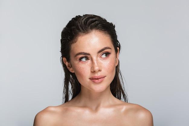 Schönheitsporträt einer attraktiven lächelnden jungen topless brunettefrau, die lokalisiert auf weiß weg steht