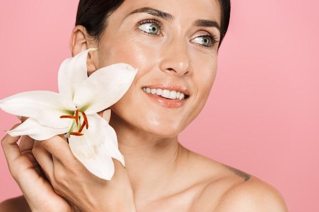 Schönheitsporträt einer attraktiven lächelnden sinnlichen brünetten schulterfreien frau, die isoliert steht und mit lilienblume posiert