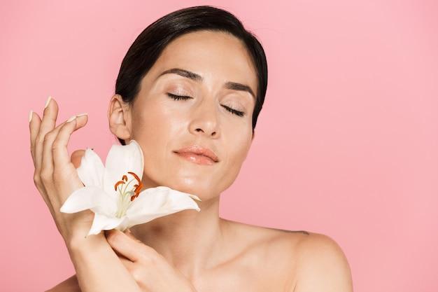 Schönheitsporträt einer attraktiven sinnlichen brünetten oben ohne frau, die isoliert steht und mit lilienblume posiert, die augen geschlossen