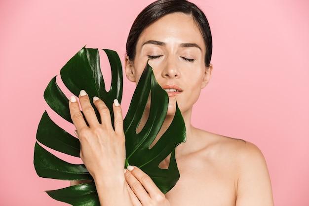 Schönheitsporträt einer attraktiven sinnlichen brünetten schulterfreien frau, die isoliert steht und mit grünem tropischem blatt posiert