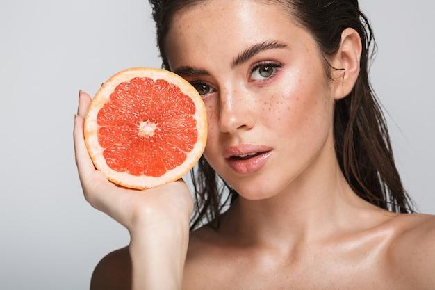 Schönheitsporträt einer attraktiven sinnlichen jungen frau mit nassen brünetten langen haaren, die isoliert auf grau stehen und halbierte grapefruit zeigen, posieren