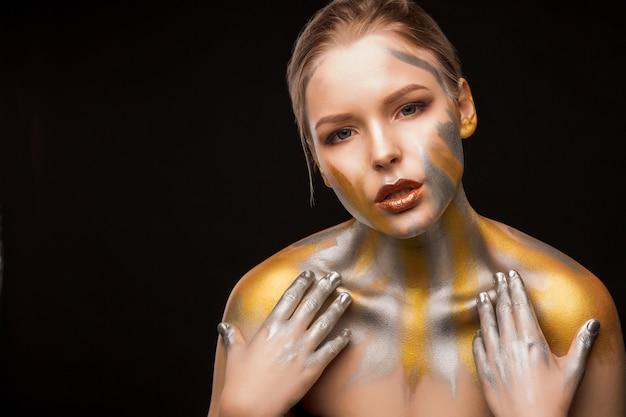Schönheitsporträt einer entzückenden blonden frau mit gold- und silberfarbe auf schultern und gesicht. platz für text