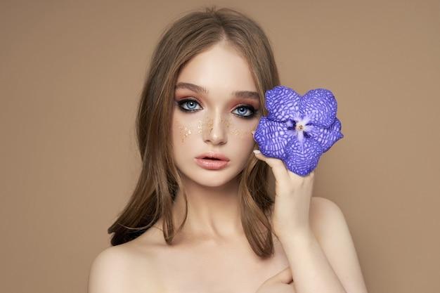 Schönheitsporträt einer frau mit einer blauen vanda-orchidee in der hand. naturkosmetik aus blütenblättern, saubere zarte haut des mädchengesichts