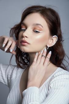 Schönheitsporträt einer frau mit natürlichem make-up und gemalten polierten nägeln auf ihrer hand.