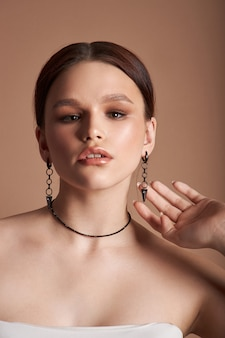 Schönheitsporträt einer frau mit schmuck, ohrringen in ihren ohren und einer halskette um ihren hals. perfekt saubere gesichtshaut, naturkosmetik