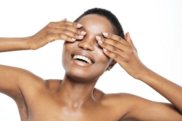 Schönheitsporträt einer fröhlichen afroamerikanischen frau, die ihre augen isoliert auf weißem hintergrund bedeckt