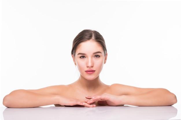 Schönheitsporträt einer jungen attraktiven halbnackten frau mit perfekter haut, die über weiße wand aufwirft und wegschaut
