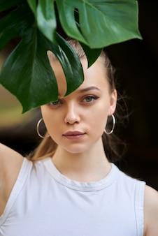 Schönheitsporträt einer jungen gesunden attraktiven blonden frau, die lokal steht und blume nahe ihrem gesicht hält