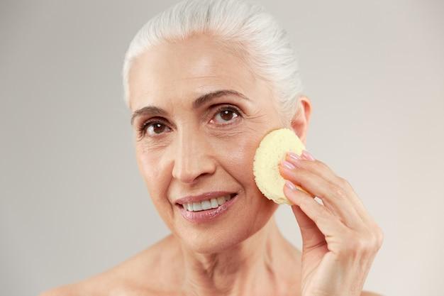 Schönheitsporträt einer lächelnden halbnackten älteren frau, die make-up-schwamm an ihrem gesicht verwendet und kamera betrachtet