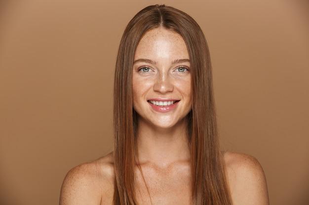 Schönheitsporträt einer lächelnden jungen topless frau mit dem langen roten haar, das aufwirft, hält hände an ihrem gesicht lokalisiert über beige wand