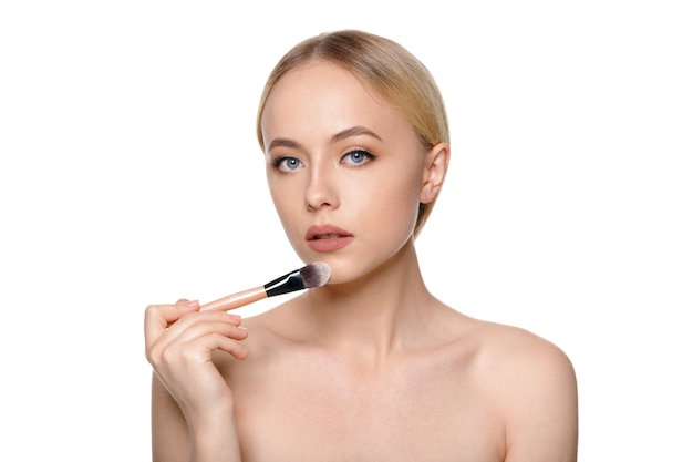 Schönheitsporträt einer lächelnden schönen halben nackte, die mit make-upbürsten aufwirft