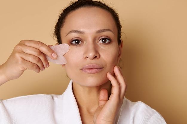 Schönheitsporträt einer mischrassefrau, die gua-sha für die lymphdrainage-gesichtsmassage verwendet. spa- und hautpflegekonzepte. kopfschuss