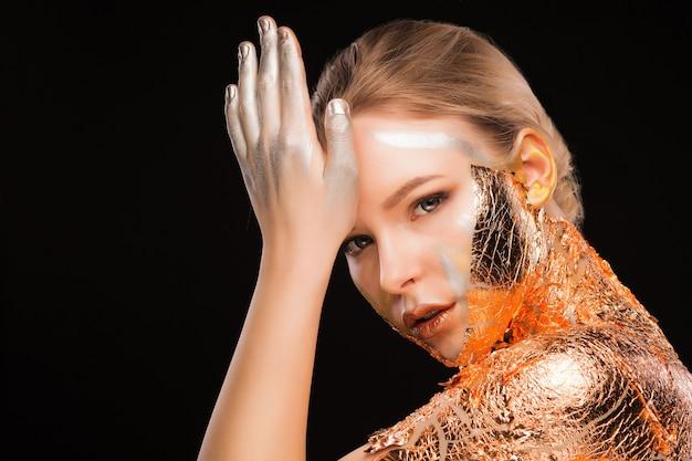 Schönheitsporträt einer modischen blonden frau mit kreativem make-up und goldfolie an hals und schultern. platz für text