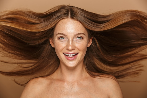 Schönheitsporträt einer schönen gesunden jungen frau mit dem langen roten haar, das kamera betrachtet, lokalisiert über beige wand