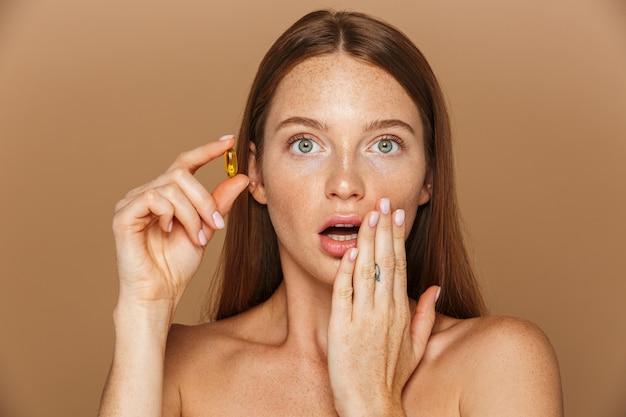 Schönheitsporträt einer schönen gesunden jungen frau mit dem langen roten haar, das vitaminkapsel lokalisiert über beige wand zeigt