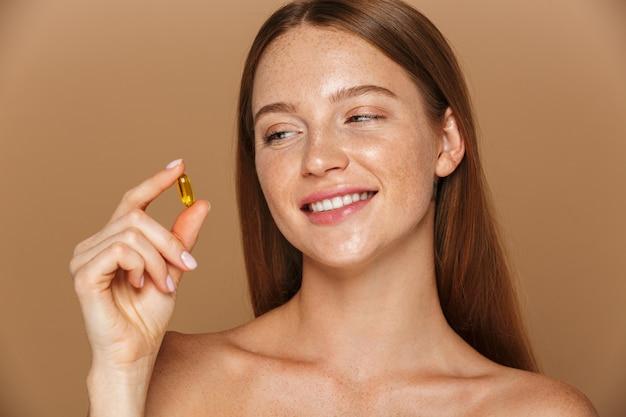 Schönheitsporträt einer schönen gesunden jungen topless frau mit dem langen roten haar, das vitaminkapsel lokalisiert über beige wand zeigt