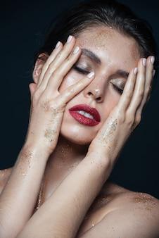 Schönheitsporträt einer zarten jungen frau mit glitzer-make-up, die ihr gesicht mit beiden händen über der schwarzen oberfläche berührt