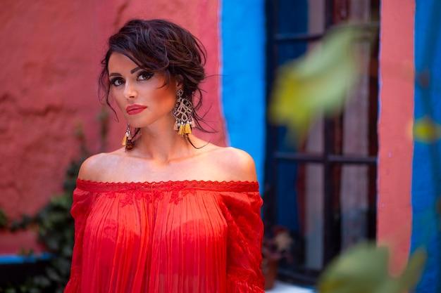 Schönheitsporträt eines schönen sinnlichen brünetten mädchens, mit make-up und modischem rotem outfit. zigeunerstil.