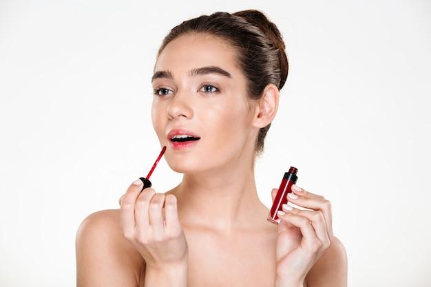 Schönheitsporträt eleganter halbnackter dame mit dem haar im brötchen, das den roten lipgloss beiseite schaut aufträgt