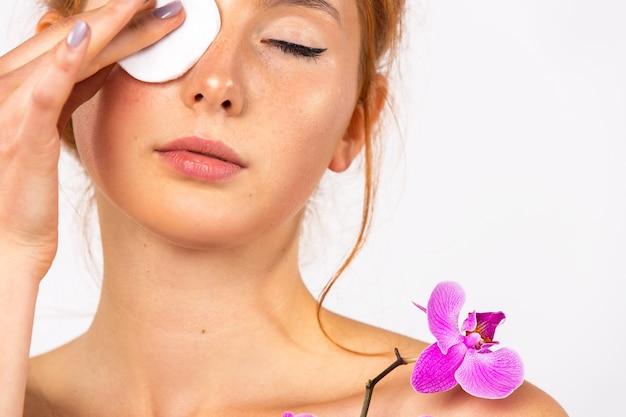 Schönheitsporträt. frauen make-up entfernt make-up mit wattepads für eine klarere und weichere haut. isoliert auf einer weißen wand. hautpflegekonzept. hochwertiges foto