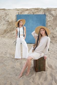 Schönheitsporträt im freien auf sand vor blauem hintergrund, junge hübsche zwillinge mit langen blonden haaren, die im sandsteinbruch in eleganter weißer, beiger kleidung aufwerfen. identische kaukasische schwestern posieren in hüten