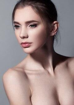Schönheitsporträt mit natürlichem make-up auf grau