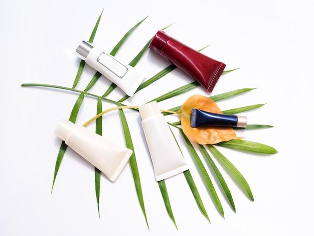 Schönheitsprodukte mit cremetube, körperlotion, gesichtsreinigungsschaum, kosmetik auf bambusblättern.