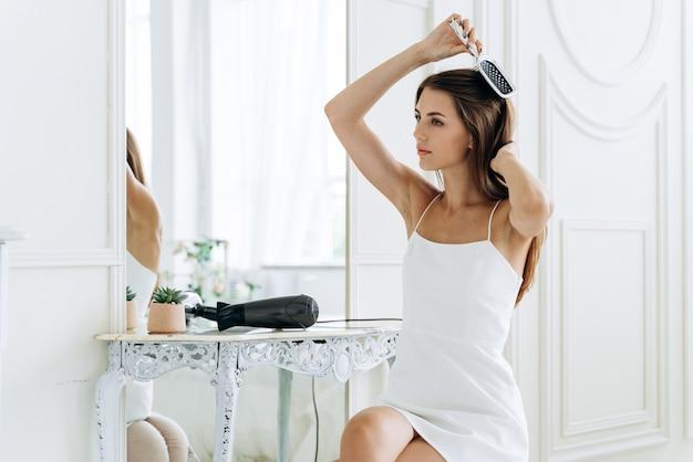 Schönheitsroutine. winsome kaukasierin, die wegschaut und ihre haare kämmt, während sie sich zufrieden fühlt. frau, die sich nach der dusche um ihren chevelure kümmert. lifestyle-konzept